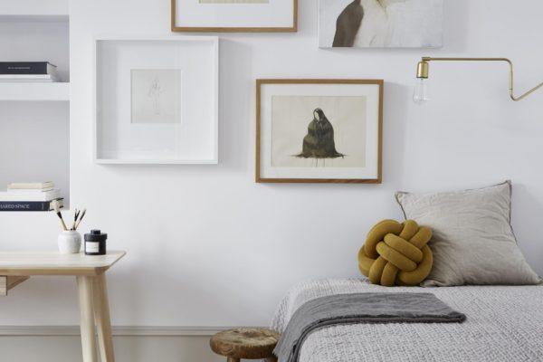 flot billedvæg med illustrationer i trærammer og sengen i soveværelset.