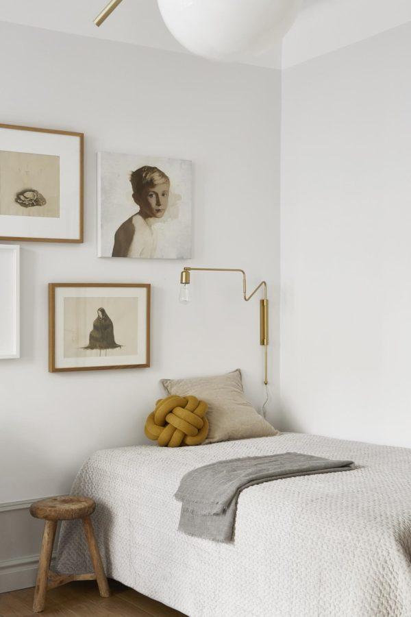 soveværelse i stuen holde i naturfarver. på væggen omkring sengen ses en flot billedvæg