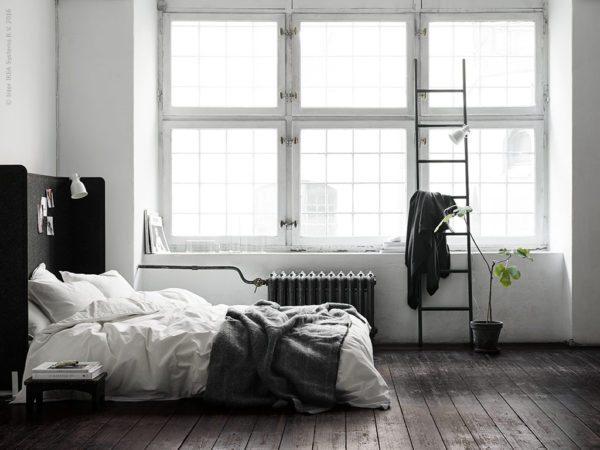Råt soveværelse med højt hovegærde lavet ud af afskærmingssvæg fra Ikea