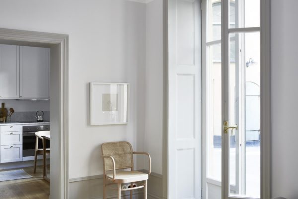 Hjørne i stue ved altanudgang. Væggene er holdt hvide og de høje paneler er lysegrå