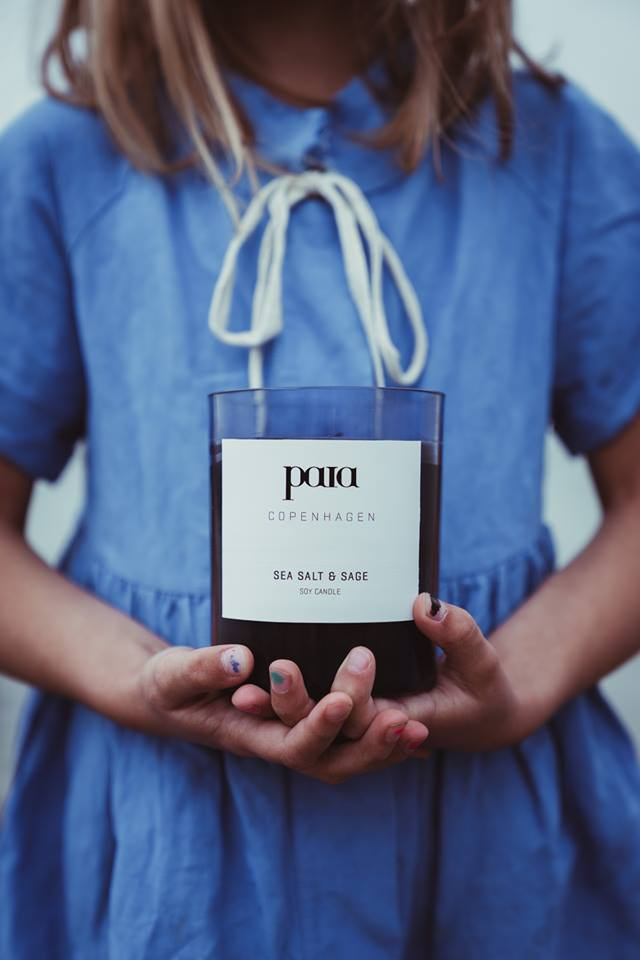 Lillepige iført blå lærredskjole holder i hænderne er smukt soyaduftlys fra Paia Copenhagen