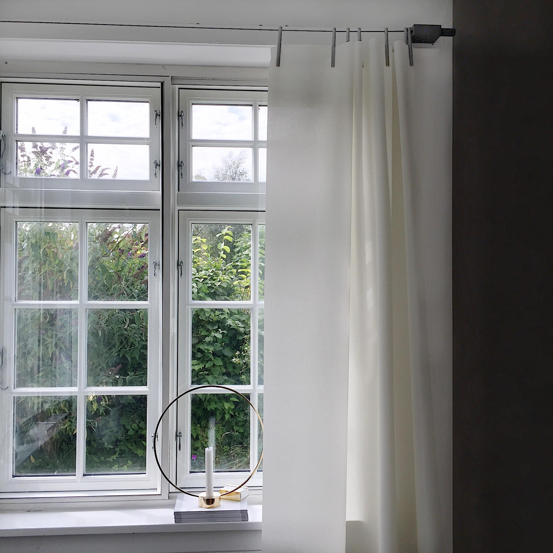 Billede af et vindue med sprossede vinduer og smukke hvide gardiner designet af Ronan & Erwan Bouroullec i kvadrat stof . I vindueskarmen ses den flotte Klong lysestage.