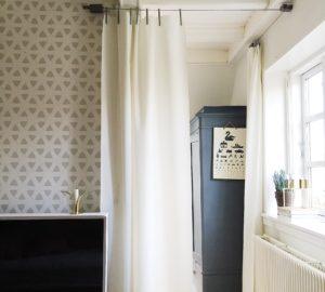 Et kig fra soveværelse ind i børneværelse. På væggen tapet fra By Lassen, og gardiner fra Kvadrat er brugt i stedet for en dør.