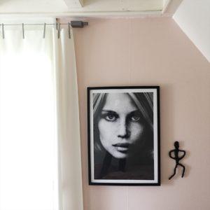 Her ses en lyserød væg med fotoportræt af en kvinde i ramme. For vinduet hænger Ronan & Erwan Bouroullec gardiner designer for Kvadrat.