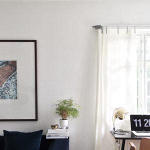 Her ses hjørnet af en blå velour sofa. Over sofaen hænger et smukt maleri af Marian Torp og til højre i billedet ses sprossede vinduer med kvadrat gardiner