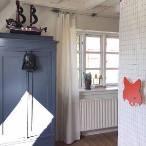 Børnværelse med flot blåmalet karlekammerskab. På skabet hænger en Batman maske
