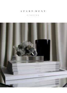 På billedet en stak bøger med et duftlys og en smuk krystal papirvægt, designet af svenske Apartment stories