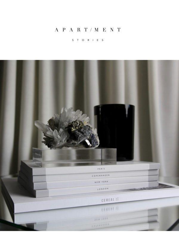 Design objekter. På billedet en stak bøger med et duftlys og en smuk krystal papirvægt, designet af svenske Apartment stories