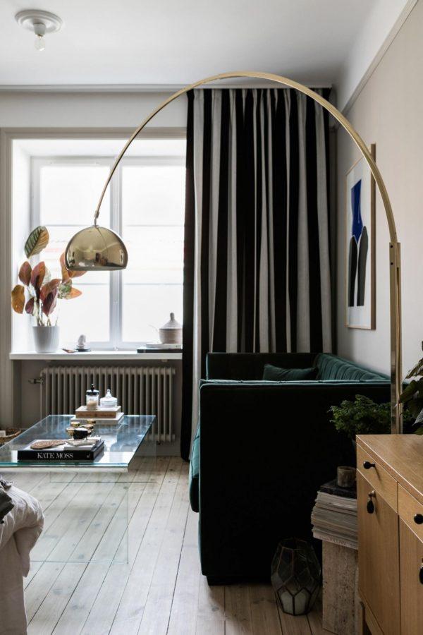 Stue med grøn velour sofa og art deco lampe i messing. Flotte gulvlange gardiner giver stuen hygge og elegance