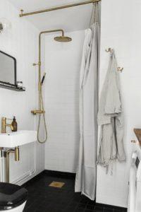 Flot hvidt badeværelse med hvide fliser fra gulv til loft og messing armatur
