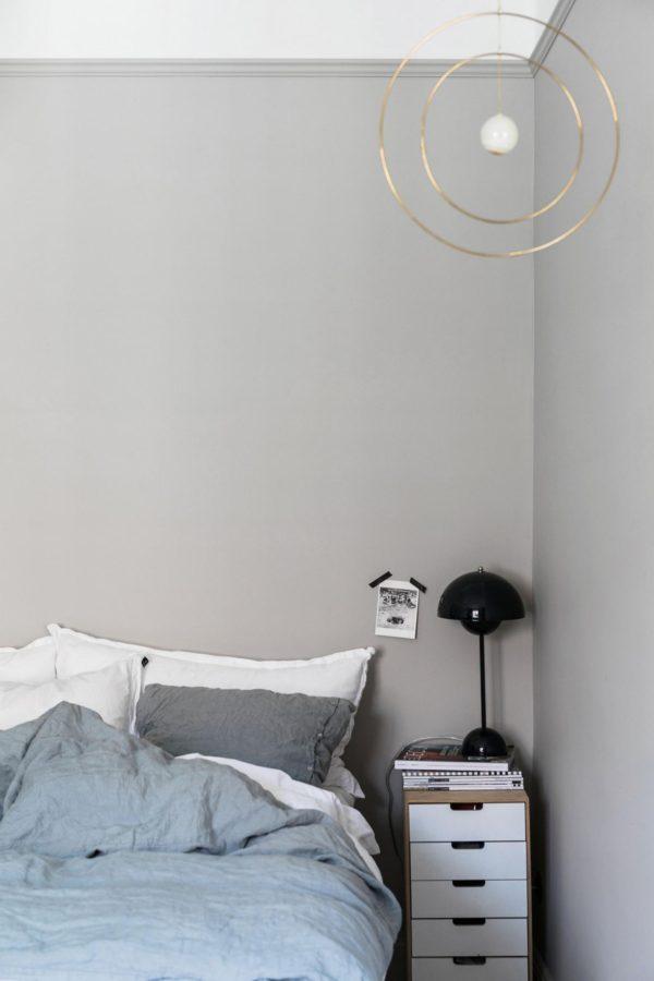 Hjørne i soveværelse med køligt grå vægge i betonlook.