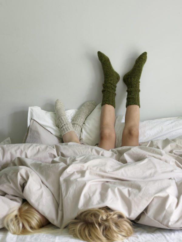 Børn i sengen med benene op af væggen og tykke uldsokker på