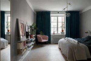 Soveværelse med med væghængtereoler fuld af bøger.