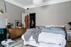 Her ses et soveværelse placeret i stuen. Sengen står op af en lys kølig går væg.