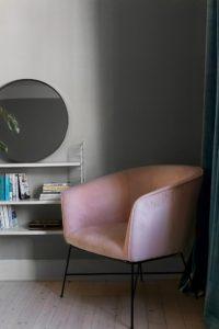 Lyserød lænestol i hjørnet i en hyggelig stue med lysegrå vægge.