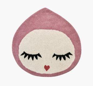 yndigt dråbeformet gulvtæppe til børnværelset i lyserødt og hvidt. Tæppet har et ansigt illustreret med lukkede øjne og lange øjenvipper
