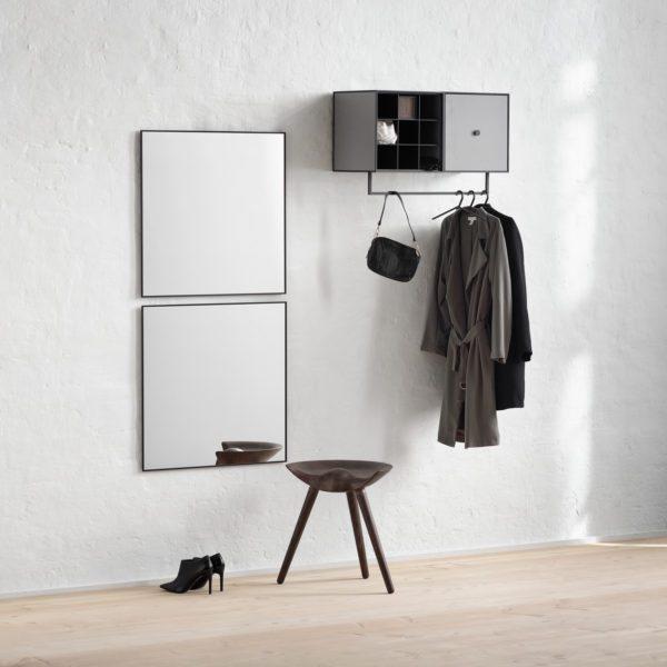 Lille entré med to kubistiske enkle spejle hængende over hinanden. Højt på væggen til højre fra spejlene hænger et dobbelt vægskab og på skabet underside er monteret en bøjlestang til overtøj.