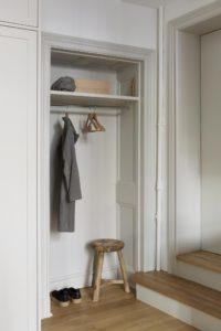 Lille entré i køkkenet med plads til bøjlestang og hylde