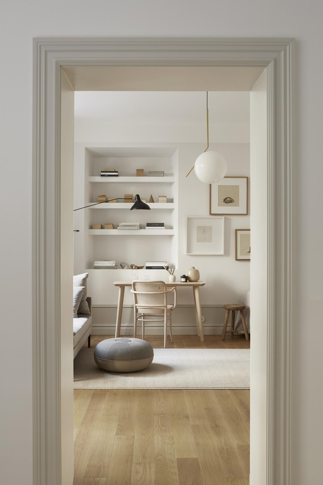 Et smukt kig ind i en lys stue med indbygget reol. Indretingen er holdt i naturfarver.