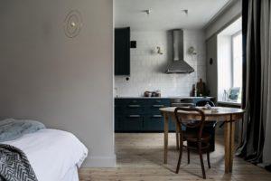 Kig fra stue ind i køkkenalrum. Køkkenet har hvide slagterfliser helt op til loftet og skabslågerne er malet i en flot grøn farve.