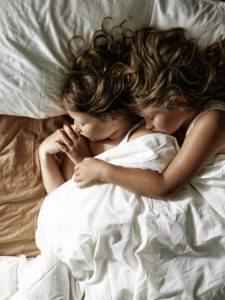 To små børn der sover arm i arm
