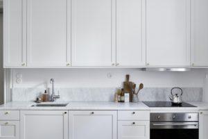Lyst og lækker køkken med marmor fliser på væggen