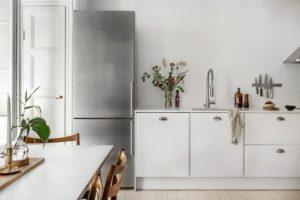 Stilrent hvidt køkken med køleskab i børstet stål. Lys og let indretning.