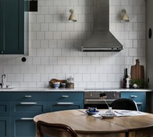 Køkken med hvide slagterfliser og mørkegrønne skabslåger. I køkkenet ser man også at der plads til et rundt spisebord
