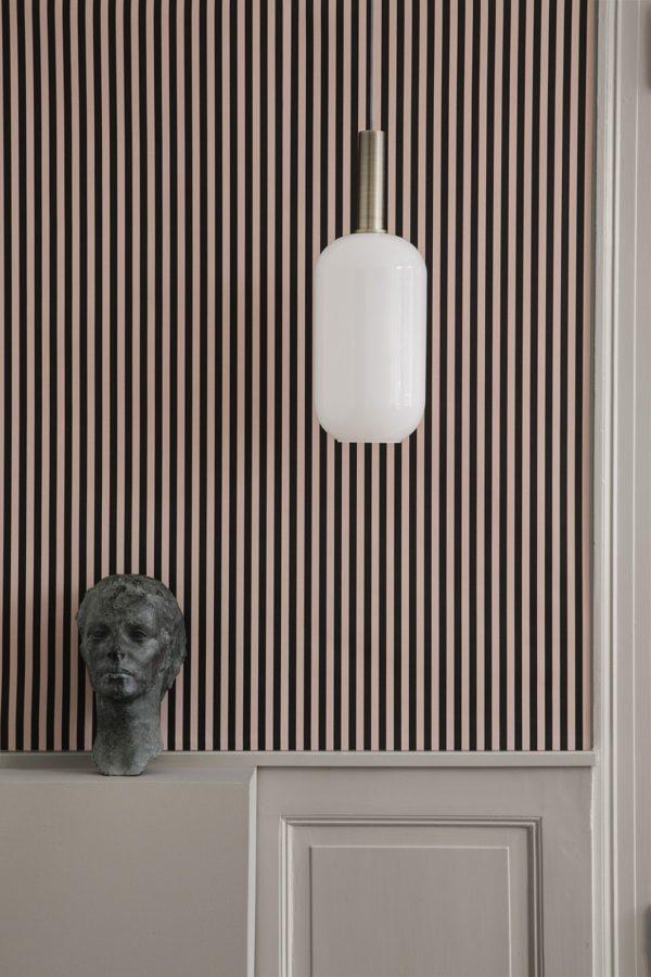 Smuk hvis aflang glaspendel som hænger i i et smukt rum med højepaneler og et flot stribet tapet i mørk og pudderfarvede striber