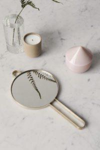 Et rundt håndspejl med messing hank, ligger meget dekorativt ved siden af et duft lys og en lågkrukke
