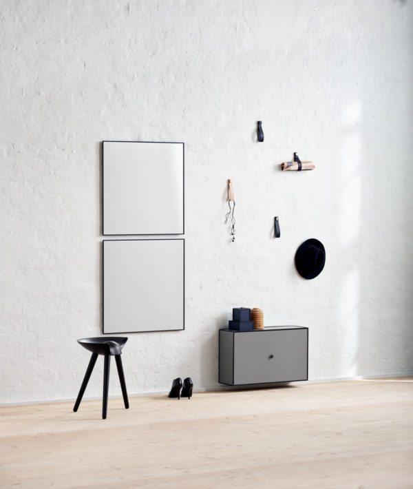 Entré med lavthængende skoskab i grå fra by Lassen. På væggen hænger også to kvadratiske spejle over hinanden og til opbevaring af tøj, nøgler og post, ses flere af By Lassens læderstropper monteret på væggen.