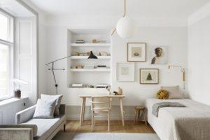 Her ses stue, soveværelse og kontor i et rum. Alt er lyst og naturligt i farverne og rummet virker lyst og venligt
