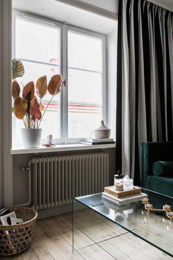 Her ses en vindueskarm i en stue med lange gardiner og en flot buket i vindueskarmen