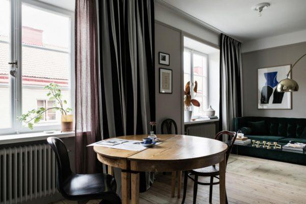 På billedet ses et rundt spisbord i træ og store vinduespartier med stribede gardiner