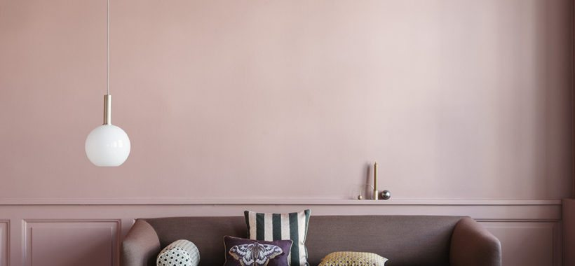 Støvet lyserød stue med høje paneler i samme farve. Mørk bordeaux sofa står op af væggen med mønstrede puder i.