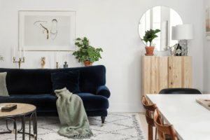 stue med hvide vægge og flot mørkeblå velour sofa. Over sofaen hænger et billede af et par fotograferede sko.