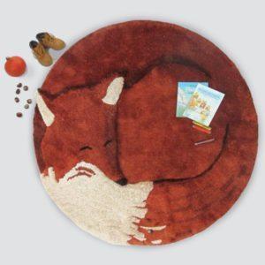 Fine rundt gulvtæppe til børneværelset i orange røde farver. Tæppet illustrerer en røv der er rullet helt sammen og sover.