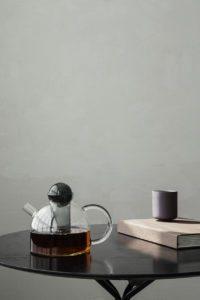 På billedet ses en tekande i glas ra Ferm Living placeret samme men en kop på et bord foran en støvet grøn væg