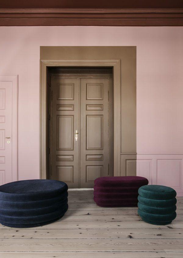 Flot støvet lyserødt rum med brun dør. På gulvet står en velour puffer i flere størrelser.