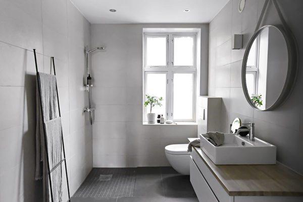 Super smukt badeværelse med store hvide fliser og mørke gulvfliser.
