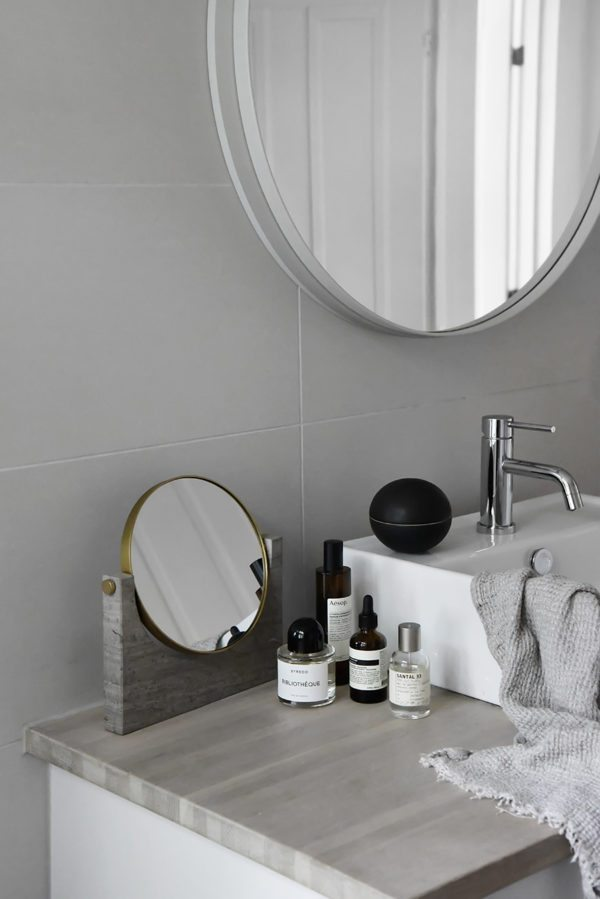 Et billede af en håndvask og lidt bordplads med et smukt spejl fra menu og lækre produkter fra bl.a. Aesop