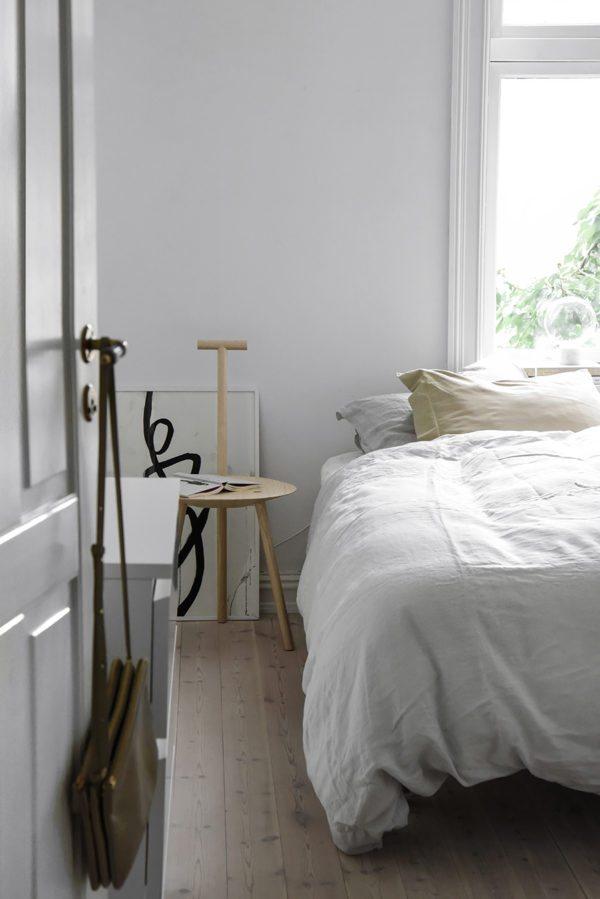Stilrent soveværelse med seng klædt i hvid og natur farvet hør. Som natbord en skulpturel skammel i lys træ