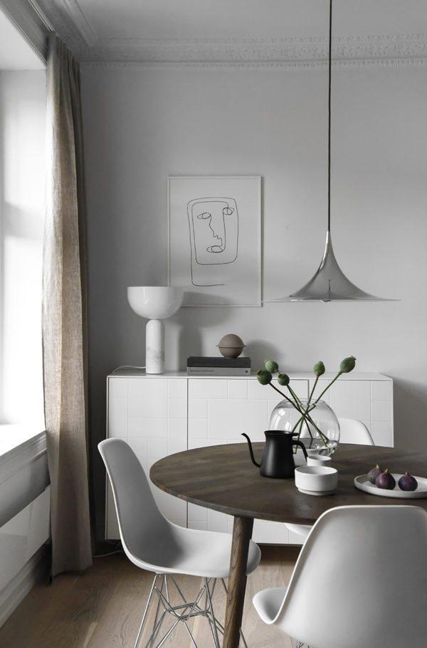 smuk og minimalistisk spisekrog med rundt mørkt træbord og en skænk i baggrunden med en flot lampe og en illustration indrammet på væggen