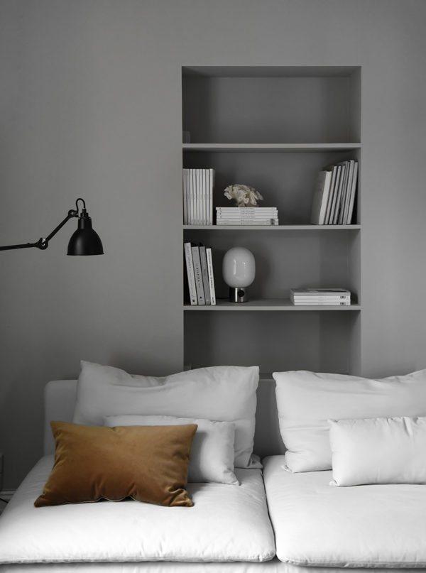 sofakrog med indbygge reol. Væg og reol er grå og fyldt med smukke blade og en fin lampe