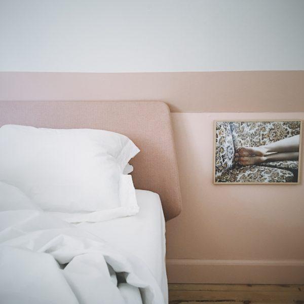 soveværelse i pudderfarver. Væg malet i pudder og sengen fra Auping med polstret hovedgærde er også pudderfarvet