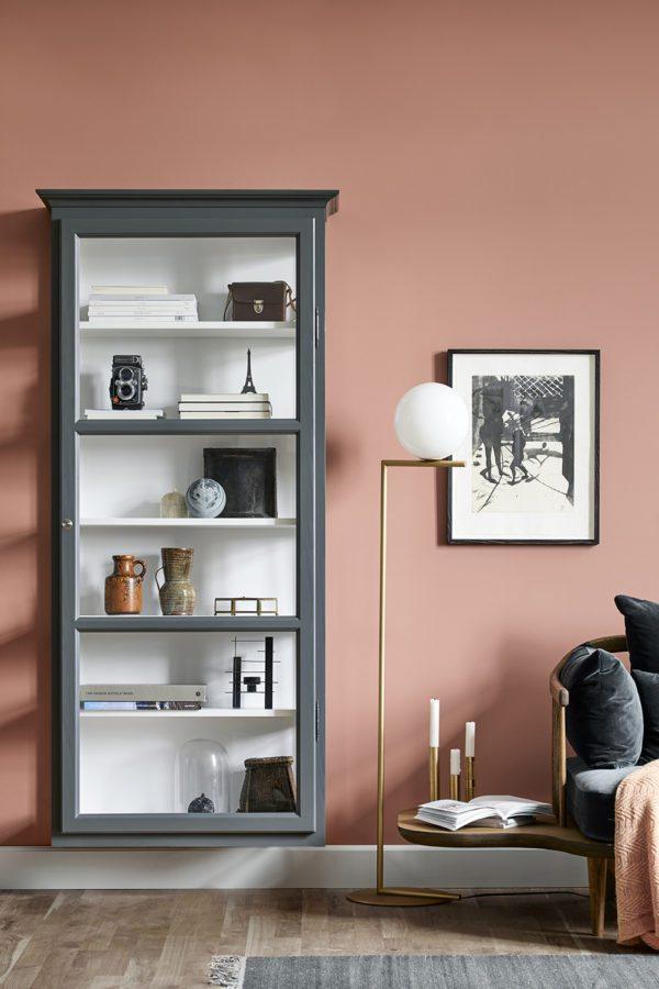 Smuk stemningsfuld stue malet i en lys terracotta farve. På væggen hænger et mørkegråt vitrineskab fra Lindebjerg Design. I skabet er en samling af keramik, loppefund, souvenirs og bøger. På gulvet står en smuk standerlampe på messingfod fra Flos og man aner lige den skulpturelle sofa FLY fra And Tradition.
