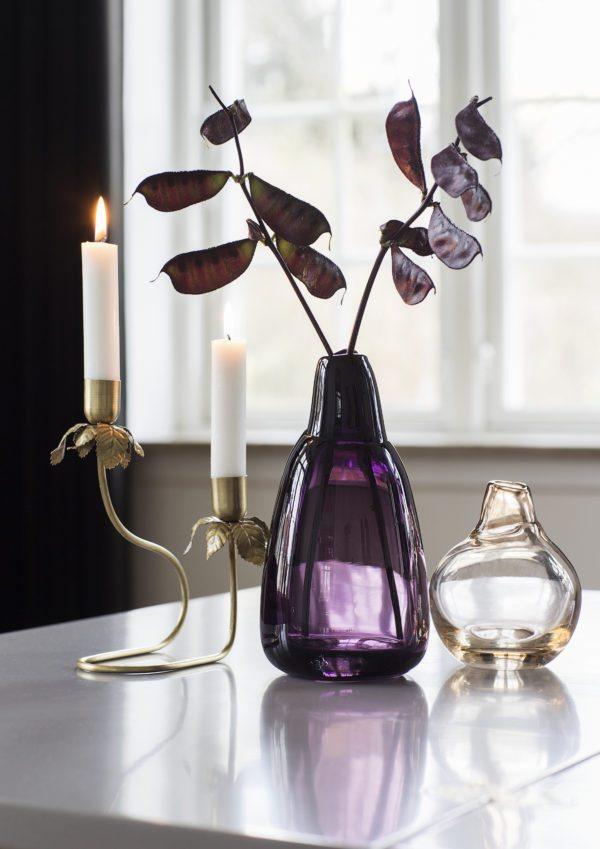 Et stilleben på spisbordet bestående af en butte lilla glasvase med to grene, ved siden af en lav buttet vase i glas og en to-armet stage i messing