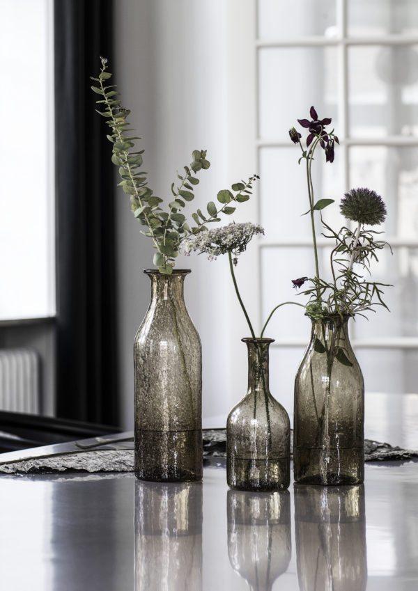 På et spisevord ses tre smukke røgfarvede glasvaser med guld mønster. I vaserne set enkelte blomster i efterårets farver.