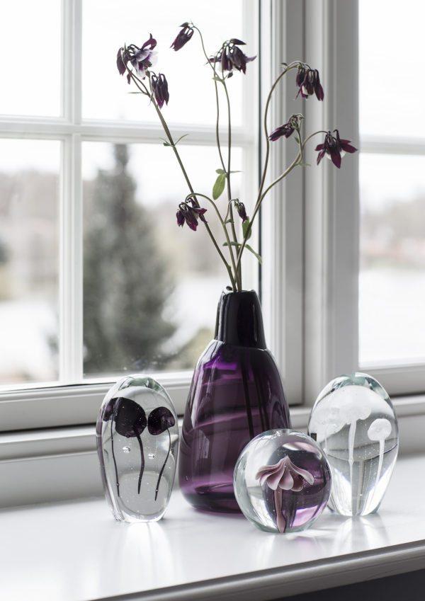 En vindueskarm med smukke gals brevvægte sammen med en lila vase.