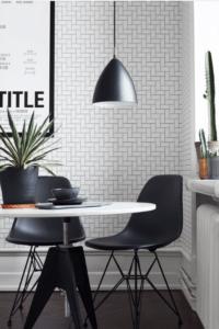 Her ses et køkken, med et rundt hvidt spisebort, sorte eames stole og sort lampe, på væggen hænger tapet med flisemøsnter